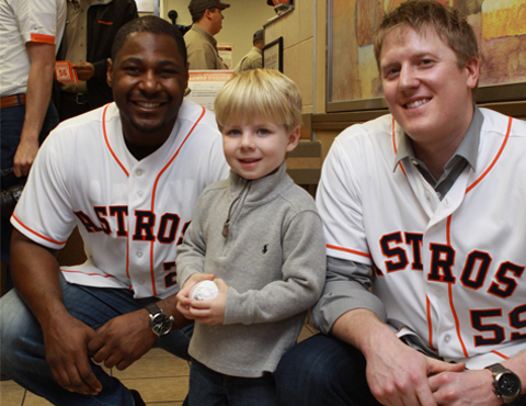 Chris Carter (left) and Marc Krauss took a break from serving Whataburger customers to take a photo with a young Astros fan in Rockport.