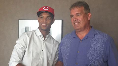 Jose Israel Garcia stands with Reds director of international scouting Tony Arias after signing his contract.