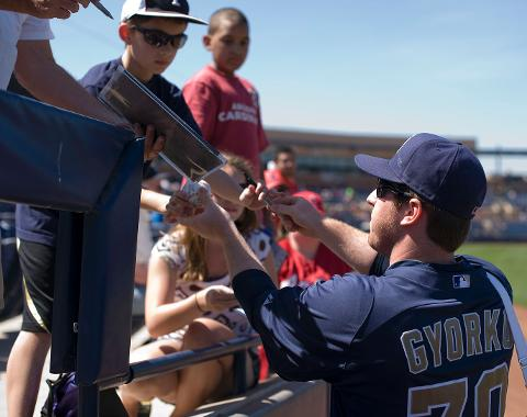 Padres infielder Jedd Gyorko hands an autographed baseball back to a young fan Friday.