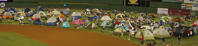 Many tents set up on the outfield of a baseball field.