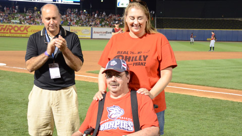Steve Paul, seated, receives his prize with his daughter Robyn, and Reichel Funeral Home owner Kevin Reichel in the middle of the sixth inning