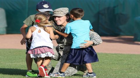 Technical Sgt. Ashley Reese embraces her three children Luke (10), Micah (6) and Leia (3) following a seven-month deployment in Qatar. Luke and Micah each threw out a first pitch before the Cougars game on July 14 followed by their mom coming out of the dugout to surprise them with her homecoming (Kane County Cougars - Donnell Collins)