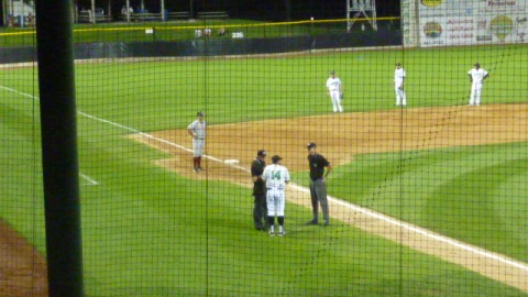 Timber Rattlers manager Matt Erickson and members of the Clinton LumberKings look on as Clinton manager Eddie Menchaca discusses Tyrone Taylor's ninth inning home run with the umpiring crew on Thursday night.