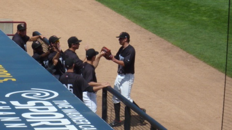 Tyler Wagner is greeted by his teammates as he reaches the dugout after coming out of Tuesday's game. Wagner got the win in Wisconsin's 5-3 decision over the Kane County Cougars.
