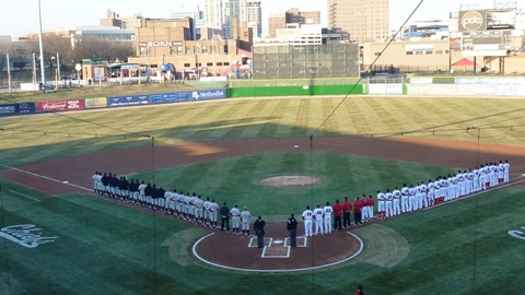 The Wisconsin Timber Rattlers and Peoria Chiefs lineup for the National Anthem before the season opening game.